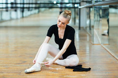 Ballerina tying pointe shoes. Beautiful ballerina tying pointe shoes in ballet class royalty free stock image