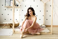 Ballerina tying pointe shoes. royalty free stock image