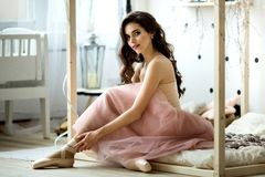 Ballerina tying pointe shoes.Portrait of young beautiful girl royalty free stock images