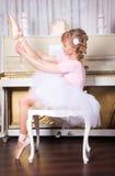 Ballerina tying pointe shoes Royalty Free Stock Photos