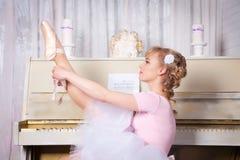 Ballerina tying pointe shoes Stock Photo