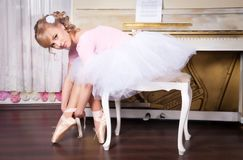 Ballerina tying pointe shoes Stock Photo