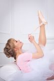 Ballerina tying pointe shoes Royalty Free Stock Photo