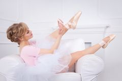 Ballerina tying pointe shoes Stock Images