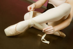 Ballerina tying the ribbon on her ballet slippers Royalty Free Stock Photography