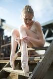 Ballerina tying the ribbon on his white pointe Royalty Free Stock Images