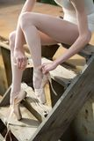 Ballerina tying the ribbon on his white pointe Stock Photography