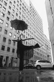 Ballerina with umbrella on city street under water drops Stock Photos