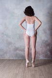 Ballerina in un costume da bagno bianco con un bello corpo che sta sulle scarpe del pointe Fotografie Stock Libere da Diritti