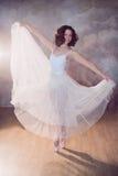 Ballerina in un costume da bagno bianco con un bello corpo che sta sulle scarpe del pointe Immagini Stock Libere da Diritti