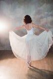 Ballerina in un costume da bagno bianco con un bello corpo che sta sulle scarpe del pointe Fotografia Stock