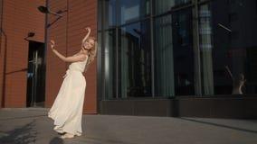Ballerina in un vestito volante che balla meravigliosamente sulla via video d archivio