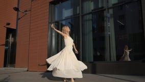 Ballerina in un vestito volante che balla sulla via nella città archivi video