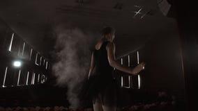 Ballerina ?va hennes flyttningar i m?rk studio Ung flickadans med den vita kl?nningballerinakjolen f?r luft som omkring rotera oc stock video
