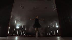 Ballerina ?va hennes flyttningar i m?rk studio Ung flickadans med den vita kl?nningballerinakjolen f?r luft som omkring rotera oc arkivfilmer