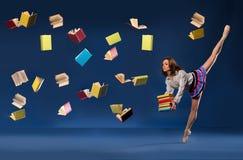 Ballerina in vorm van schoolmeisje met stapelboeken stock foto's