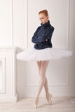 Ballerina in a warm pullover. Pretty young ballerina standing by the fireplace. A girl wearing a tutu and black sweater stock photo