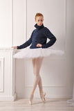 Ballerina in a warm sweater. Pretty young ballerina standing by the fireplace. A girl wearing a tutu and a black sweater Stock Photo
