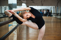 Ballerina warming up. Beautiful ballerina warming up in ballet class royalty free stock images