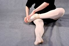 Close-up of a ballerina feet in pointe. Ballerina warming up feet before the rehearsal. Classical school of ballet stock photo
