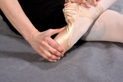 Close-up of a ballerina feet in pointe. Ballerina warming up feet before the rehearsal. Classical school of ballet stock image