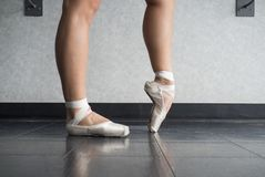 Ballerina warming up her feet in her pointe ballet shoes before class. In the dance studio royalty free stock images
