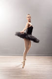 Ballerina is wearing a black tutu and pointe shoes Stock Photo
