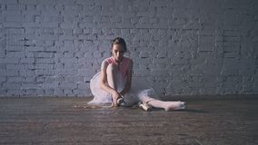 Ballerina is wearing and tying pointe shoes. Ballerina wearing pointe shoes and tying stock video footage
