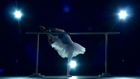 Ballerina is wearing in white dress and pointe stock video