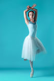 Ballerina in white dress posing on toes, studio background. Royalty Free Stock Photo