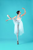 Ballerina in white dress posing on toes, studio background. Stock Photos