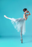 Ballerina in white dress posing on toes, studio background. Royalty Free Stock Photography