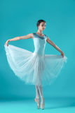 Ballerina in white dress posing on toes, studio background. Stock Photography
