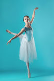 Ballerina in white dress posing on toes, studio background. Stock Images
