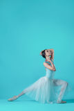 Ballerina in white dress posing on toes, studio background. Royalty Free Stock Image