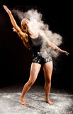 Ballerina white powder. Expressive dance movement of a female contemporary ballet dancer on stage with a black background who spread white powder by clapping Stock Images