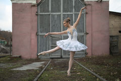 Ballerina in white tutu. Good-looking ballerina making a pose between the rails in front of technical structure in a railway depot. She is wearing a white tutu royalty free stock photography