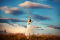 Ballerina. Woman ballerina dancing at sunset in the field stock photography