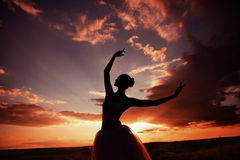 Ballerina. Woman ballerina dancing at sunset in the field stock photos