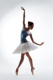 The ballerina. Young beautiful dancer jumping on a studio background Stock Photos