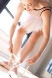 Ballerinaband snör åt av balettskor i studio Arkivbilder