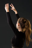 Ballerinadansare som poserar med hennes händer på ett mörker Arkivfoto