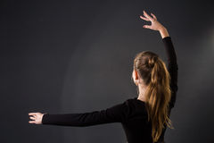 Ballerinadansare som poserar med hennes händer på ett mörker Royaltyfri Foto