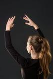 Ballerinadanser het stellen met haar handen op dark Stock Foto's