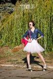 Ballerinahippie, der in Herbstpark geht skateboarding lizenzfreies stockfoto