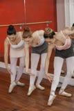 Ballerinas Bending While Performing In Dance Studio. Full length of ballerinas bending while performing in dance studio Stock Photos