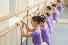 Ballerinas doing exercises at ballet barre. Lesson of classical ballet dance for children. Group of young ballet dancers Royalty Free Stock Photo