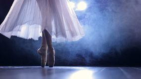 Ballerinas feet as she makes pointe arabesque steps. Pointe arabesque performed by a ballerina on a dark fogged dancing stage stock video footage