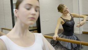 Ballerinas perform dance exercises near ballet machine and mirror. Two women in black and white ballet tutu gently move their hands during a rehearsal at stock footage