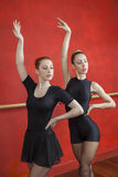 Ballerinas Practicing With Hands Raised In Rehearsal Room Royalty Free Stock Photography